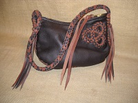 These two pictures show a dark Brown shoulder bag constructed with two-tone (dark Brown and Mahogany) leather braiding. It's 8 strand leather strap has long tassels on each end of it. It's closure is a large brass zipper that is attached with hand sewn 5 ply nylon thread ...and has a leather strap attached to its slide.