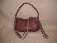 A small leather bag made with Mahogany leather. It's constructed with braided seams and has a (not so long) 8 strand leather strap ...with long tassels hanging from it's ends. The large brass YKK #10 zipper was attached with hand sewing ...and has a leather strap on the slide.