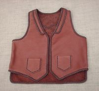 "This two tone brown moccasin cowhide leather vest has front lapels, a back pointed yoke, and front patch hip pockets (without flaps). It also has two mated inside patch pockets attached with the same braiding as these outside ones. It also has a 3"" back/bottom squared off (not curved) draft pocket. Clicking on this link will bring you to more text about it and more picturs of it."