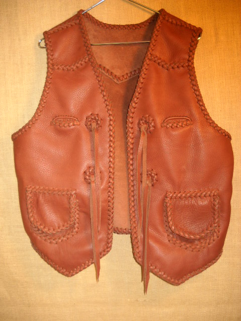 A rather Western style braided vest using moccasin cowhide leather. It has pointed front yokes, a pointed back yoke, two patch hip pockets with flaps, ans two breast pockets (credit card size). It also has straps hanging from a conchoe I fashion with a braided circle.