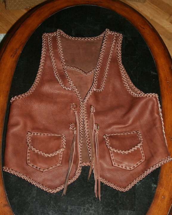 This rather Western style braided leather vest features front lapels, a back pointed yoke, patch hip pockets with flaps, and straps with solid brass D rings.