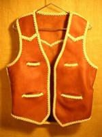 "This moccasin cowhide leather vest was made in the USA. It features both front and back yokes that are all pointed. It has two slit breast pockets (credit card size) and two slit hip pockets. It also has the curved 3"" draft flap extension at the back/bottom. Click on it for a larger view of it."